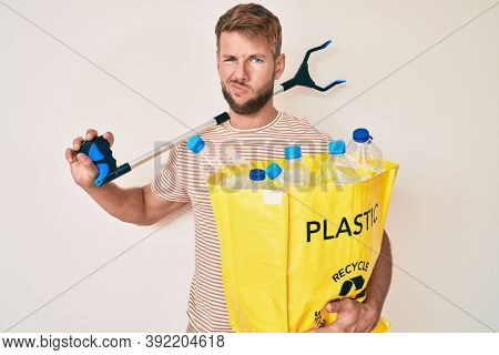 Young caucasian man holding recycling bag with plastic bottles and waste picker clueless and confused expression. doubt concept.