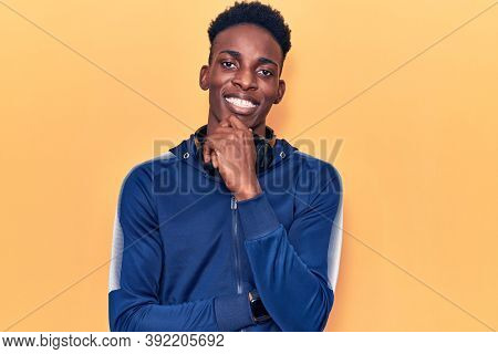 Young african american man wearing sportswear and headphones smiling looking confident at the camera with crossed arms and hand on chin. thinking positive.