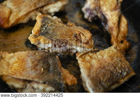 Portions Of Fish Fried To Golden Crust In  Frying Pan. Fried Fish With Appetizing Crispy Crust. Home