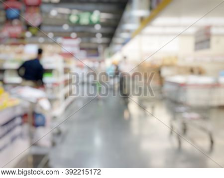 Blurred Image Of People Shopping In Supermarket. Cashier With Long Line Of People Waiting At Checkou