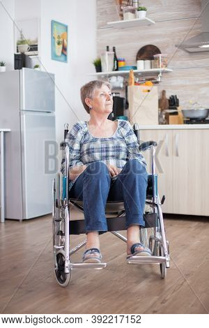 Sad Depressed Disabled Senior Woman Sitting In A Wheelchair. Elderly Handicapped Pensioner After Inj