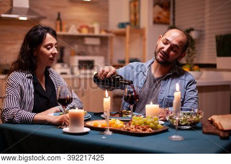 Husband Pouring Wife To Wife During Romantic Dinner In Dining Room. Young Man Pouring Red Wine In Wi