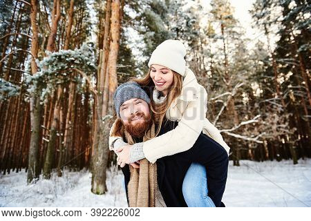 Happy Smilling Couple. Man Giving Woman Piggyback Ride On Winter Vacation In Snowy Forest. Young Cou