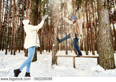 Young Couple Having Fun In Winter Forest On Vacations. Copy Space For Text. Xmas Morning. Happy Play