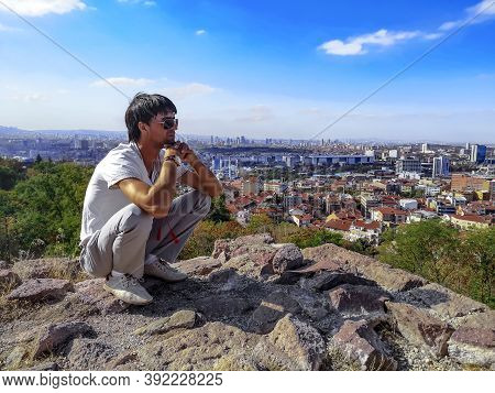 A Young Adult Man In Sunglasses Is Squatting On A Hilltop In The Center Of Ankara Overlooking The Ca
