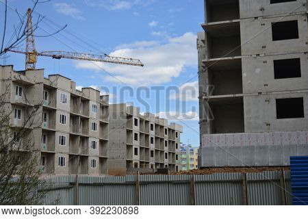 Construction Of Multi-storey Buildings. A Construction Crane Stands Among The Gray Blocks Of Buildin