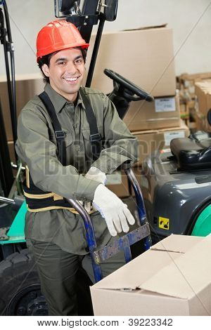 Portrait of happy young foreman leaning on handtruck at warehouse
