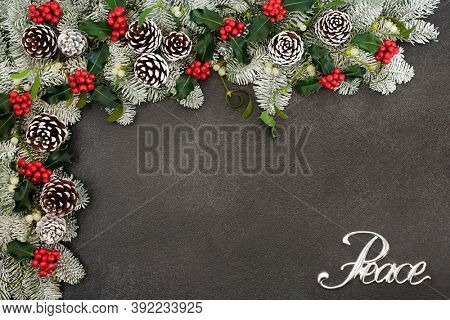 Silver Peace sign on winter, Christmas & New Year border with snow covered spruce fir, holly, mistletoe & pine cones on grey grunge background. Peace on Earth concept. Top view, flat lay, copy space.