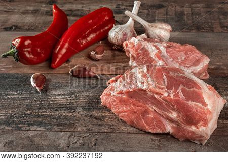 Fresh Meat With Ingredients For Cooking On Dark Background. Pepper And Garlic Ingredients For Cookin