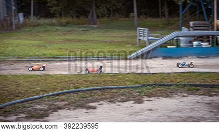Three Rc Buggies Racing On An Outdoor Offroad Track