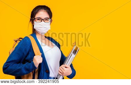 Happy Asian Female College Student Wear Protective Face Mask For Protecting Coronavirus, Holding Lap