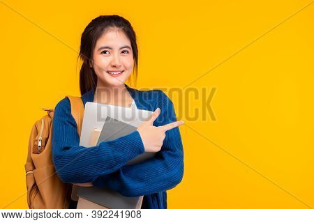 Happy Asian Female College Student Smiling At Camera On Yellow Background, Holding Tablet And Book,