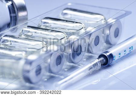 Vials With Liquid Drug As Vaccine Dose Flu Shots Along With Syringe For Injection Treatment On Medic