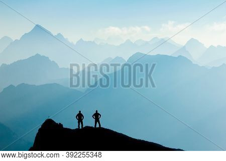 Two Men Reaching Summit After Climbing And Hiking Enjoying Freedom And Looking Towards Mountains Sil