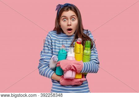 Photo Of Emotional European Housemaid Opens Mouth Widely, Stares In Stupor, Carries Bottles Of Clean