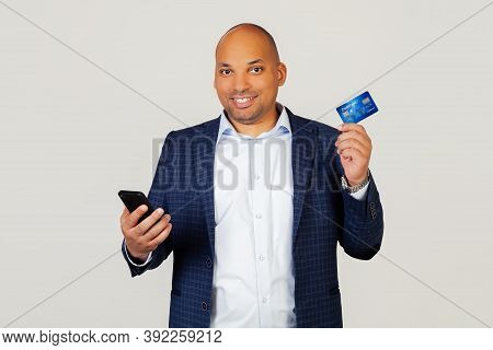 Portrait Of Happy Young African American Guy Businessman Using Credit Card To Pay Online Using Smart
