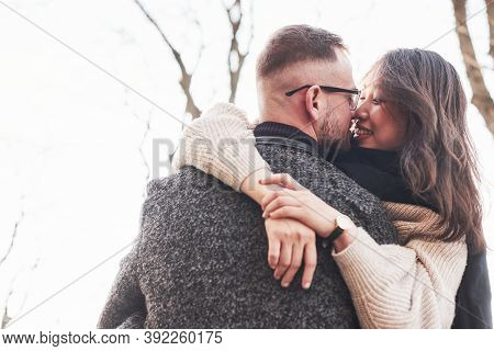 Cheerful Multiracial Couple Embracing Each Other Outdoors In The City. Asian Girl With Her Caucasian