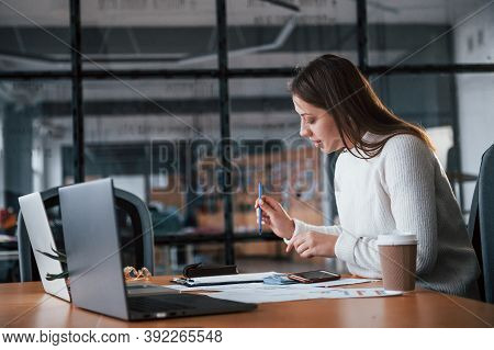 Young Girl In White Clothes Working In The Office By The Table.