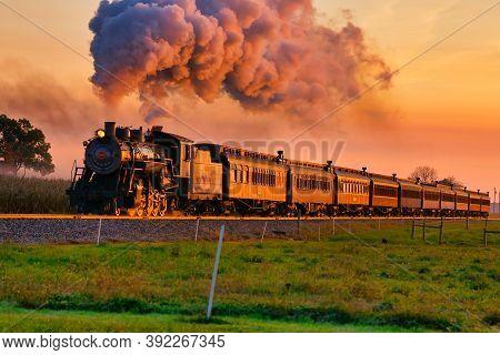 Strasburg, Pennsylvania, October 2020 - View Of Golden Steam Passenger Train At Sunrise Traveling Th