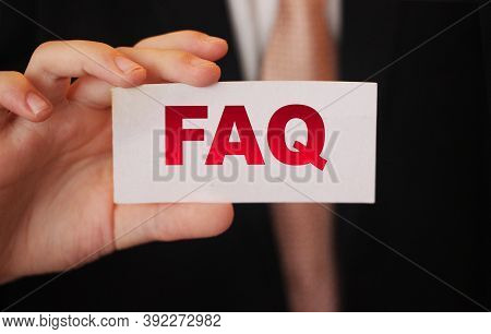 Closeup On Businessman Holding A Card With Text Faq , Business Concept Image With Soft Focus Backgro