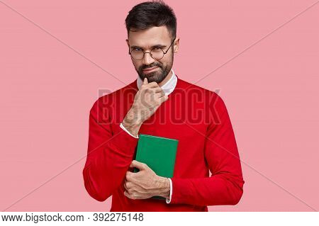 Cunny Young Male Has Intention To Do Something, Holds Chin, Carries Green Notebook For Writing Notes