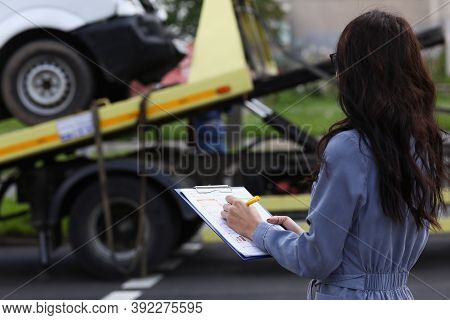 Woman Insurance Agent Prepares Documents For Car That Is Taken Away By Tow Truck. Voluntary Car Insu