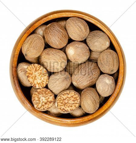 Whole And Halved Nutmegs In A Wooden Bowl. Fragrant Or True Nutmegs, Dried Seeds Of Myristica Fragra