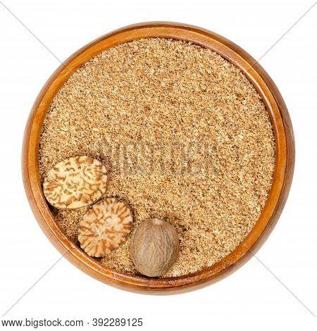 Freshly Grated Nutmeg, Whole Nutmeg And Nutmeg Halves In A Wooden Bowl. Fragrant Or True Nutmeg, See