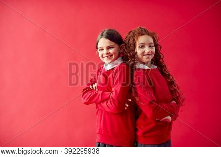 Two Elementary School Pupils Wearing Uniform Back To Back Against Red Studio Background
