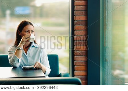 A Cute Brunette Is Resting And Drinking Coffee During A Break In A Cafe. The Concept Of Rest In A Ca