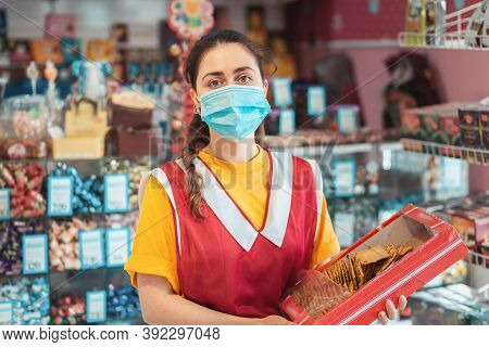 Female Worker In Uniform With A Medical Mask On Her Face, Holding A Box Of Goods. Showcase With Prod
