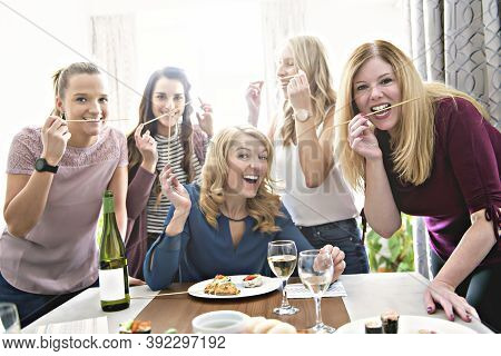 Group Of Attractive And Funny Woman Eating Sushi At Home