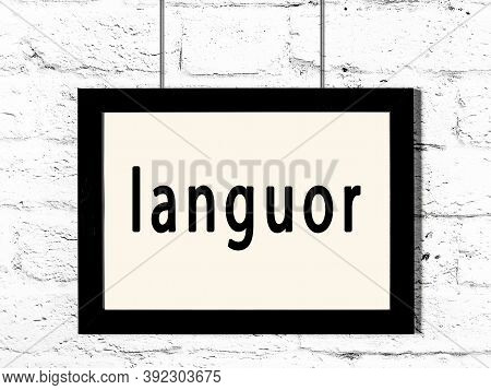 Black Wooden Frame With Inscription Languor Hanging On White Brick Wall
