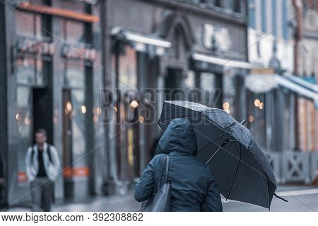 Rear View Of An Unrecognizable Woman In A Dark Winter Insulated Jacket With A Hood And An Umbrella I