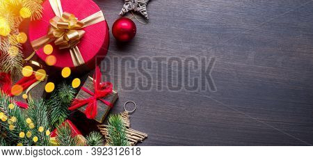 Christmas decoration, gift boxes and blurred lights on dark wooden table. Christmas or New Year holiday background shows the magic of Christmas holiday. Top view.