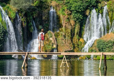 Kravica, BiH - August 31, 2019: Unidentified tourist stands on the wooden bridge in front of beautiful Kravica waterfall in Bosnia and Herzegovina. Beautiful cascade waterfall in forest