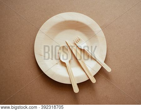 Top View Of Wooden, Biodegradable, Eco Friendly Tableware Set On The Plate On Craft Paper Background