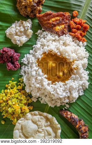 Homemade fish thali meal served at bannana leaf in Kerala state, India. Overhead view