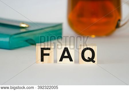 Wooden Cubes With The Inscription Faq On The Background Of A Notebook And Tea. Frequently Asked Ques