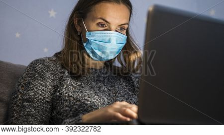 Young Business Woman In Medical Mask Working From Home With Laptop In The Evening During Self-isolat