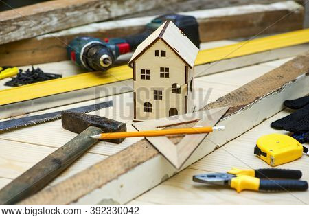 Wooden House Toy Surrounded By Tools. Concept Home Repair. Home Improvement. Renovate Home.