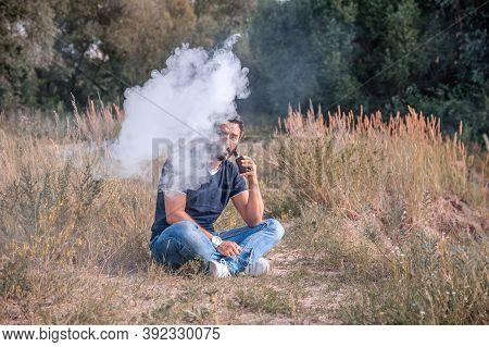 Stylish Vape Man Exhaling Vapor From Electronic Cigarette. Electronic Cigarette Concept.