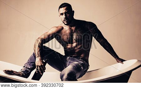 That Means Its Bath Time. Strong Latino Man With Tattoo On Muscular Torso Sitting In Bath. Atheltic