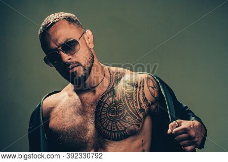 Fashionable Tattoo. Muscular Hispanic Man With Tattoo On Chest. Strong Latino Man With Tattoo On Ski