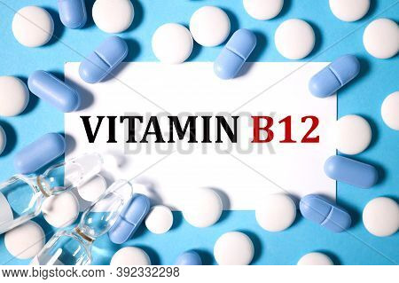 Vitamin B12, Text On White Notepad Paper On Blue Background Near Capsules And Tablets