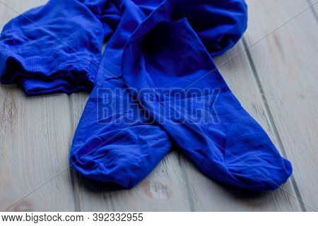 Blue Tights On Wood Background. Blue Tights As A Female Element Of Clothing. Clothes