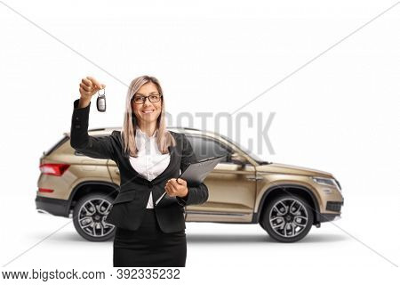 Businesswoman holding keys from a SUV isolated on white background