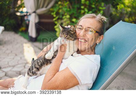 Happy Smiling Senior Elderly Woman In Glasses Relaxing In Summer Garden Outdoors Hugging Domestic Ta