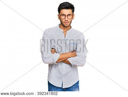 Young handsome man wearing casual clothes and glasses skeptic and nervous, disapproving expression on face with crossed arms. negative person.