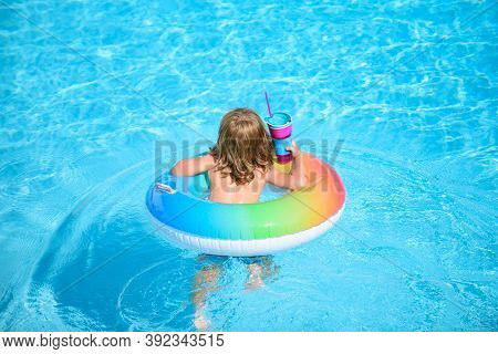 Kid With Colorful Swim Ring In Swimming Pool On Summer Day. Water Toys And Floats For Child. Healthy